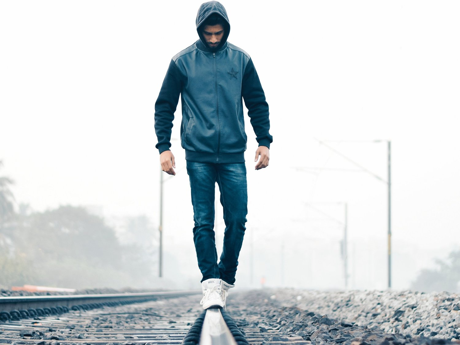 a male try to balance on a railway